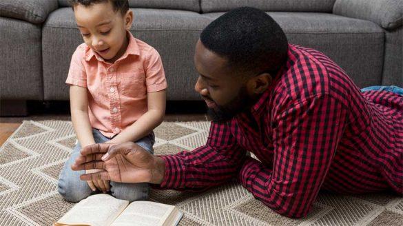 Treinamento de Pais, com Vanina de Andrade, imagem de um homem e uma criança, na sala, lendo um livro